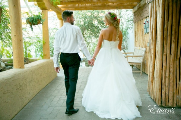 The photographer captures the bride and groom walking away, hand-in-hand and looking at each other on a back porch shaded from the sun. The bride shows off her loose fishtail hairstyle with a simple flower crown.