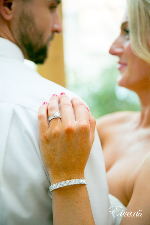 This wedding photographer makes the bride's ring a focal point while the newlyweds gaze lovingly at each other.