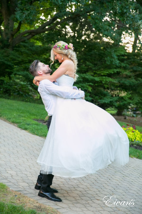 Spellbound groom romantically lifts his new bride into the air. The bride sports a bohemian look with a hot pink flower crown and a fishtail braid hairstyle.