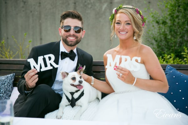 Newlyweds proudly hold their MR and MRS signs as they pose for a photo with their little dog in a tuxedo.