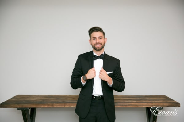 The groom grips the lapels of his tuxedo jacket and smiles broadly in front of a vintage wood table.