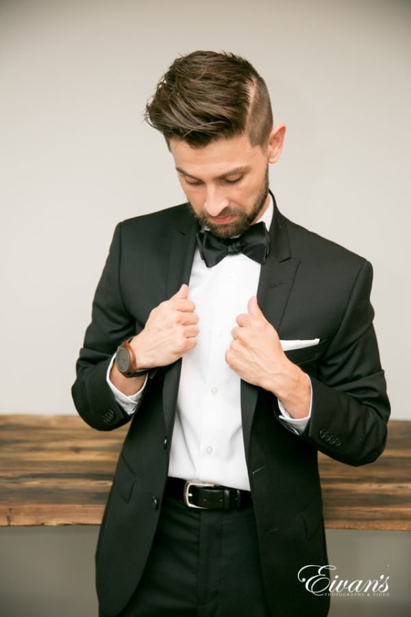 The groom cooly straightens his suit in a portrait style image.