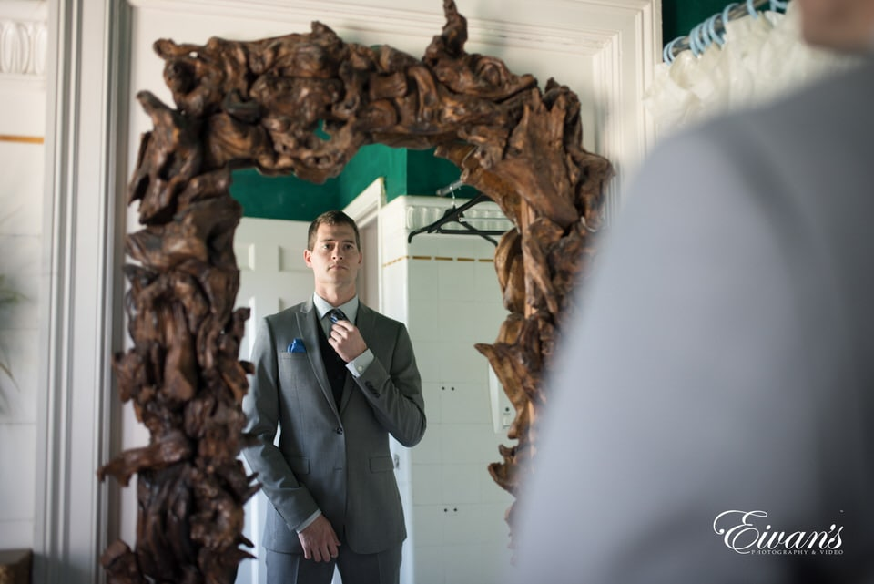 The groom prepares for his special day by straightening his tie and checking his suit. Photographer captures a reflective shot of the groom in an old, carved wood framed mirror.