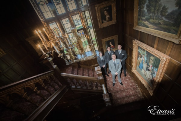 A beautiful old-aged stairwell portrait of the groom and his men.
