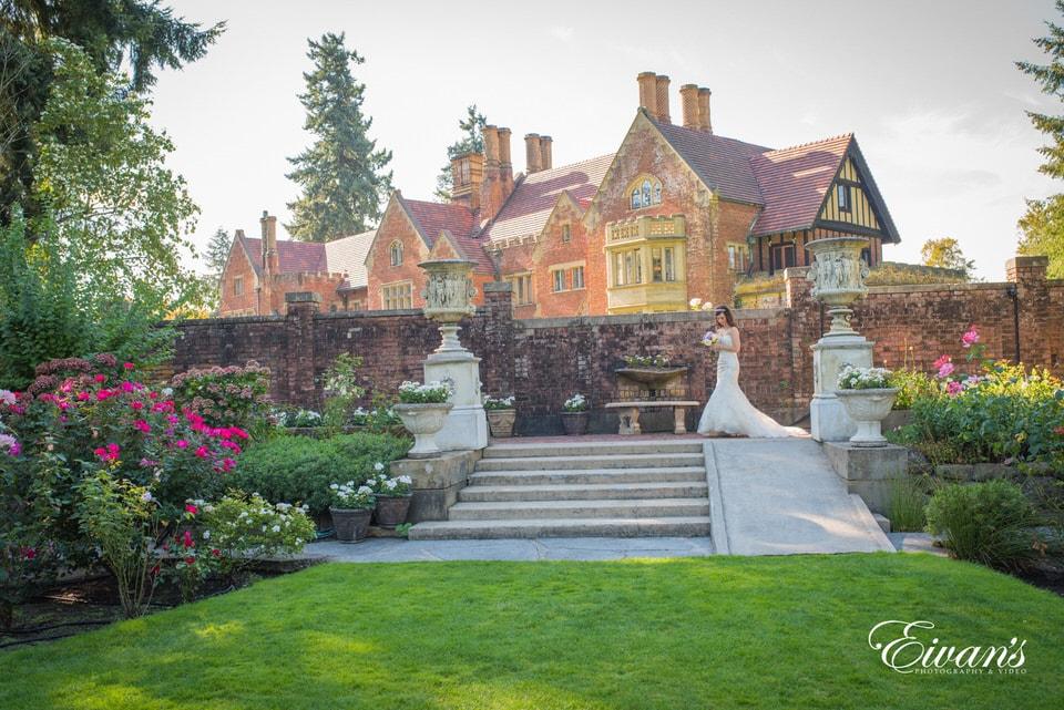 The bride walks thoughtfully through the garden of the estate.
