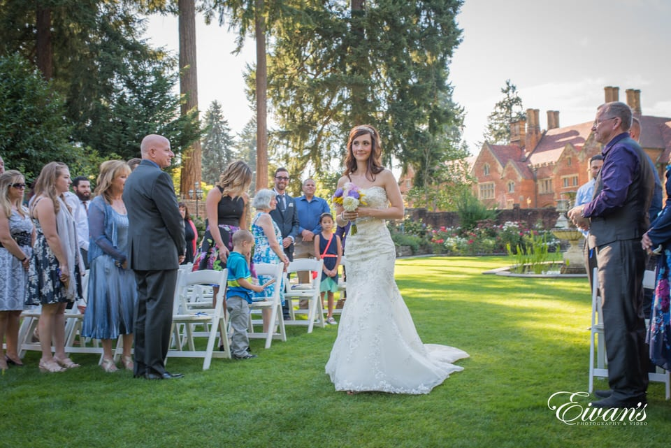 Bride strides down the aisle to her groom while the guests stand and watch her proceed.