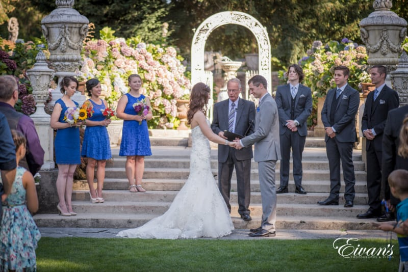 Bride and groom hold hands while standing at the alter on their wedding day.