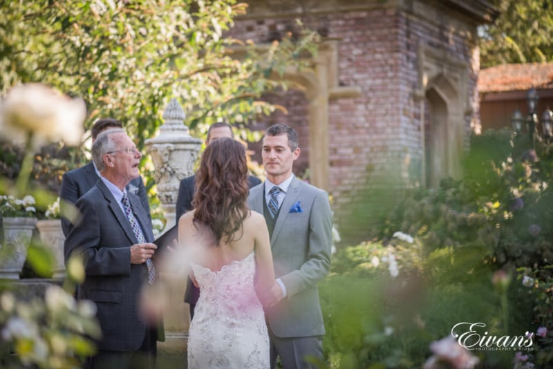 The groom looks at his bride during their wedding ceremony.