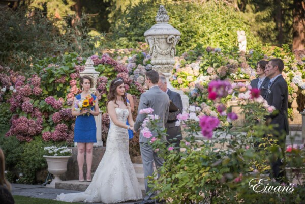 The bride and groom are sharing their vows during their ceremony in a beautiful and bountiful garden.
