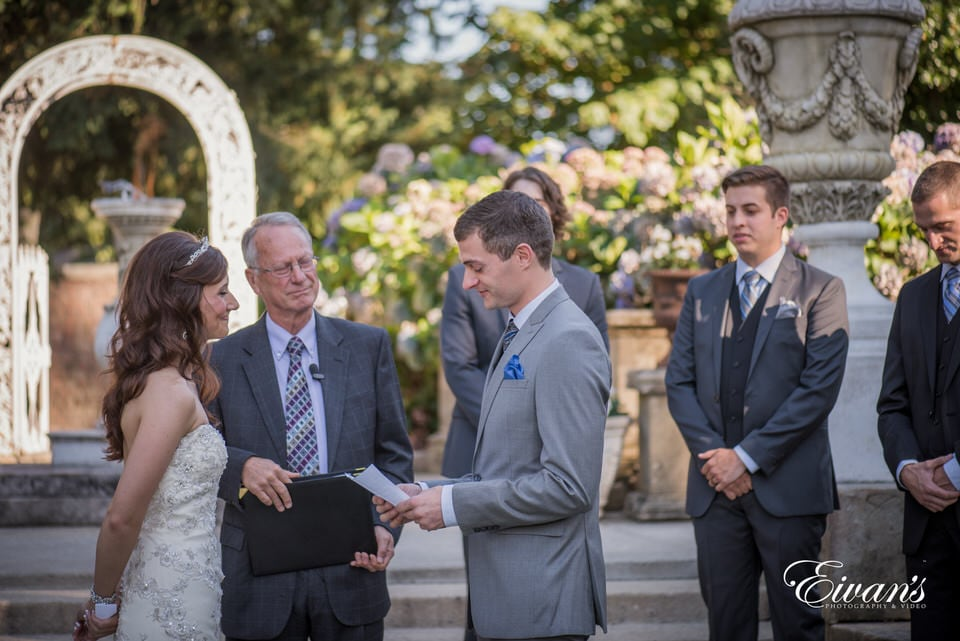 The groom reads his vows to his bride during this wedding ceremony.