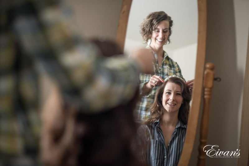 The mother of the bride joyfully helps her daughter get ready by placing her tiara as they smile and laugh in the mirror.