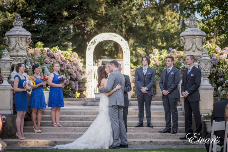 Bride and groom share their first kiss as husband and wife as the bridal party smiles at them warmly. The sun sets on the archway behind them and highlights the bountiful, purple flowers in the background.