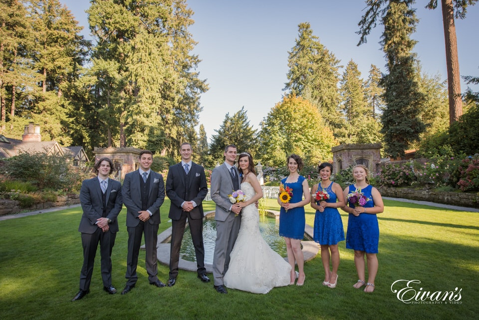 Bride, groom and bridal party pose and smile for portrait photography in front of a lovely fountain and pond.