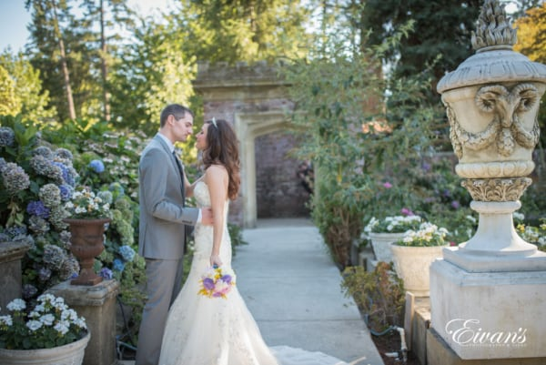 The Newlyweds share an intimate moment in the garden while funny onlookers peek around the entryway to watch.