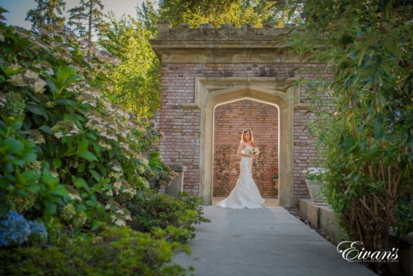 New bride poses with her bouquet in the stone entryway of a garden.