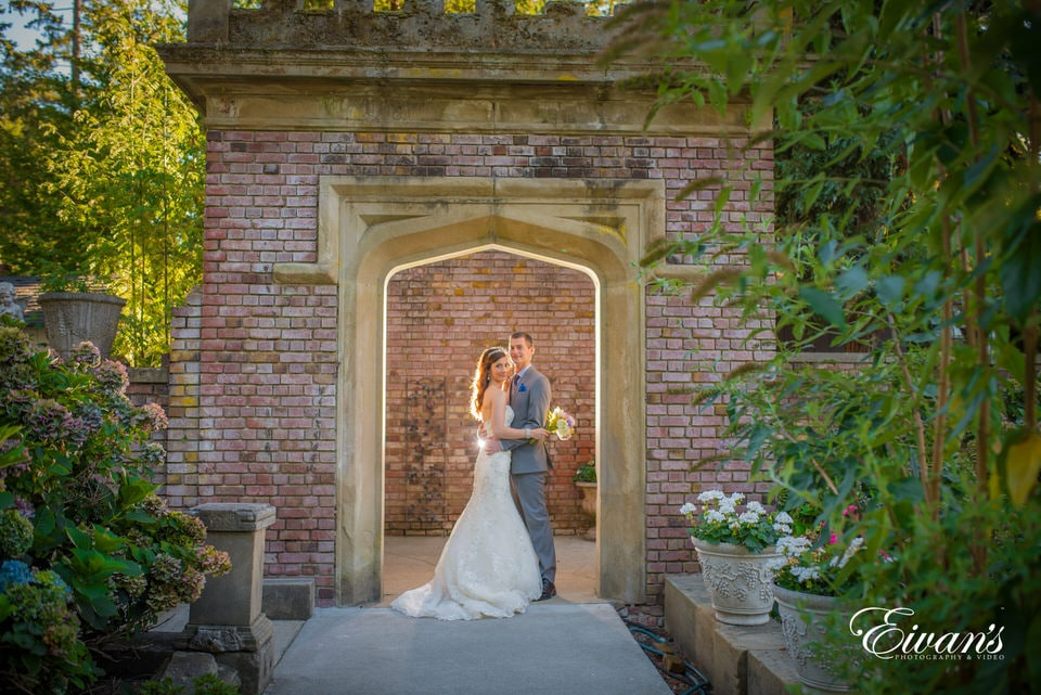 Newlyweds embrace each other beneath a well-lit entryway in the garden.