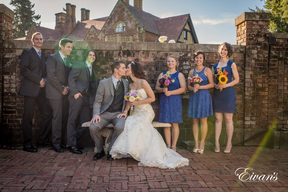 The bride and groom steal a kiss while taking bridal party portraits.