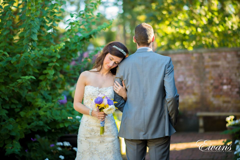 Bride thoughtfully leans on her groom's shoulder while she admires her wedding bouquet.