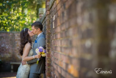 Bride and groom kiss against a brick wall.