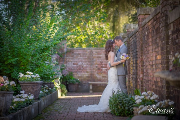 Bride and groom embrace each other for portrait photography with the bouquet in the garden.