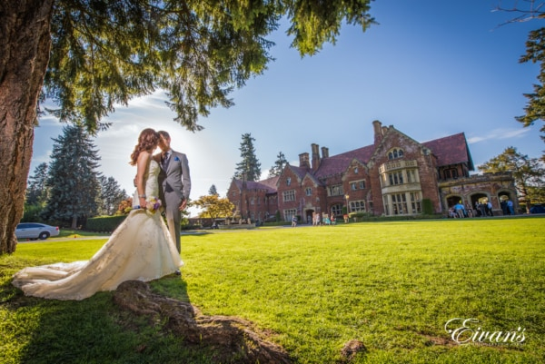 Wedding couple taking photos at the reception venue which located outside of a beautiful mansion in Seattle. Bride and groom are glowing from the sun shining on their back.
