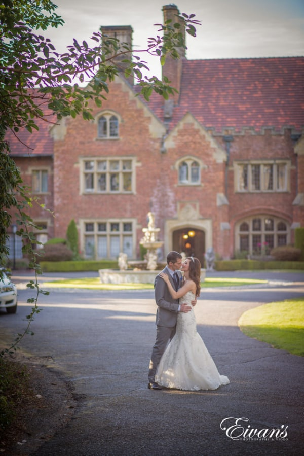 Bride and groom in a romantic embrace in the driveway of their wedding location.