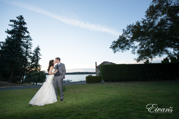 Newlyweds share a kiss on an open, grassy field overlooking a body of water at sunset.