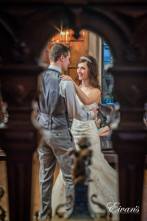 Candid photography of bride and groom dancing at the reception. The bride wears a lovely tiara and smiles adoringly at her husband.
