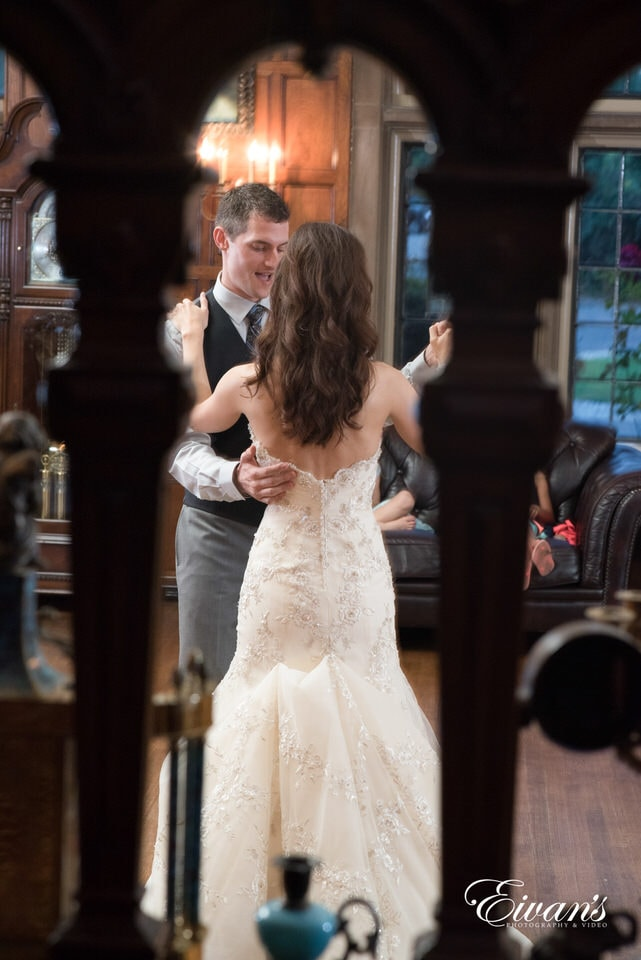 Candid photography of bride in gorgeous floral patterned and beaded wedding gown dances with her new husband at the reception.
