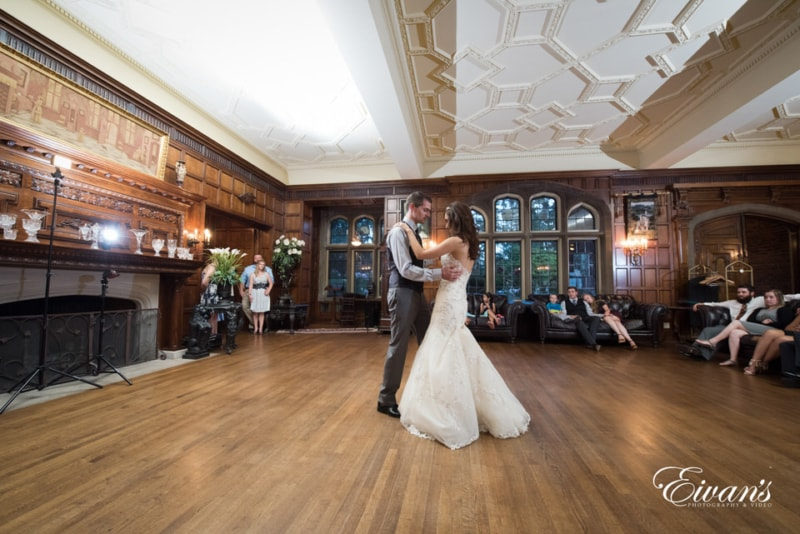 Bride and groom share a dance at their reception in an oldfashioned victorian styled home as onlookers watch leisurely.