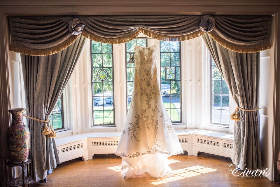 Wedding dress photography ideas. The photographer hung the dress from the drapes to highlight the floral embroidery and cut of the train.