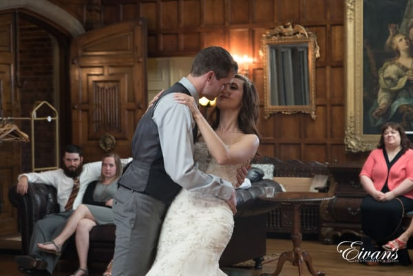 Groom dips his bride during a romantic dance at their reception in an oldfashioned Victorian style home.