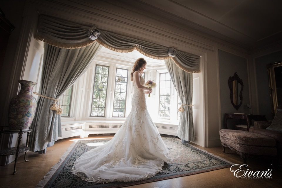 The photographer takes a stunning image of the bride looking thoughtfully at her bouquet in the middle of a vintage style room with deep bay windows. Her long train spills out on the floor beneath her.