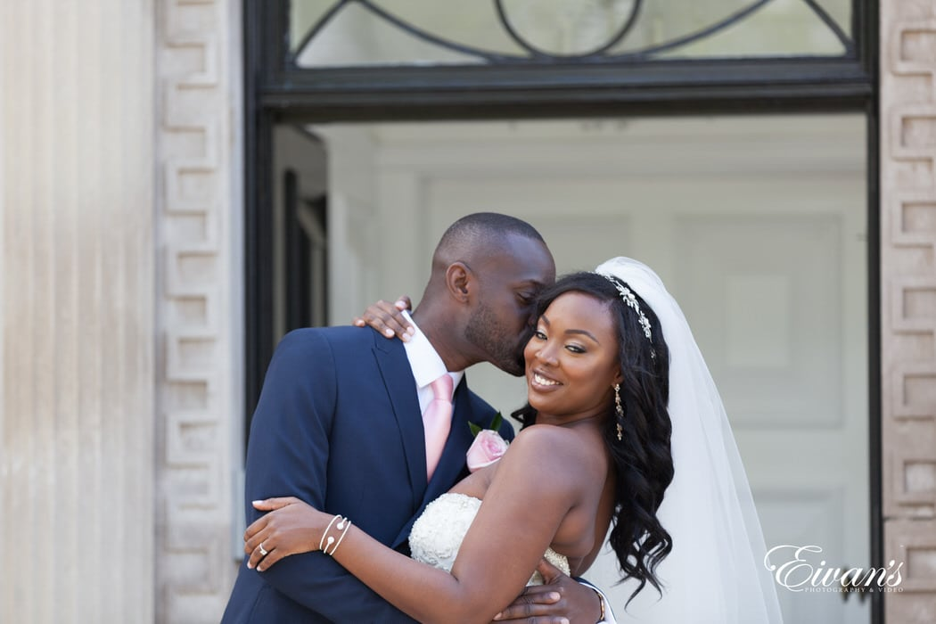 Kissing his new wife's cheek making her smile with only true love and excitement.