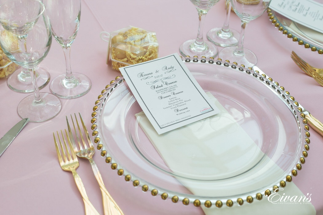 With a light pink table cloth with gold embellished glassware.