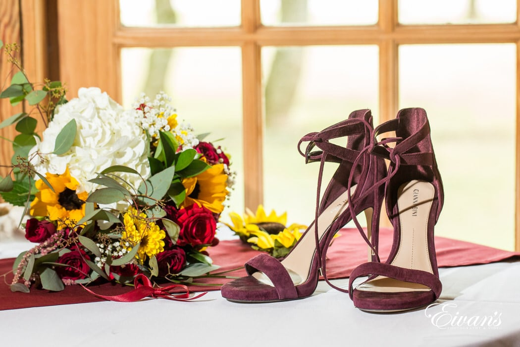 Maroon shoes placed elegantly next to sunflower assorted bouquet.