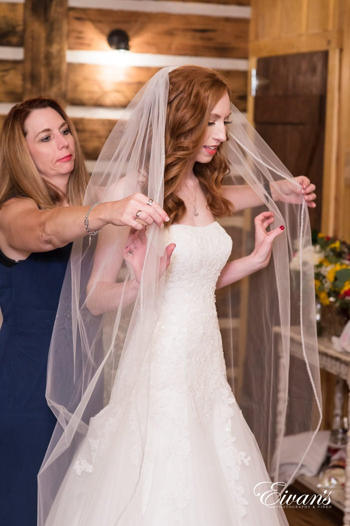 Laying the veil onto her daughter's head, the mother of the bride supports her daughter to the highest degree.
