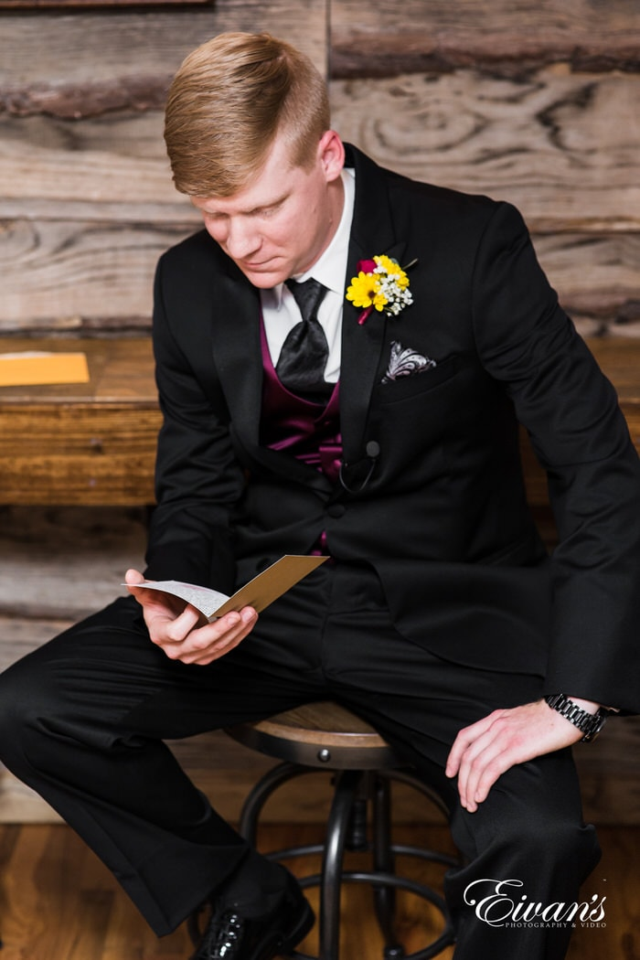 The groom reads a card written from his beloved before he sees her at the alter.