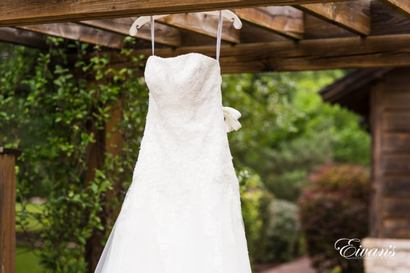 Stunning bride's gown hanging against rustic wood and vibrant greens.