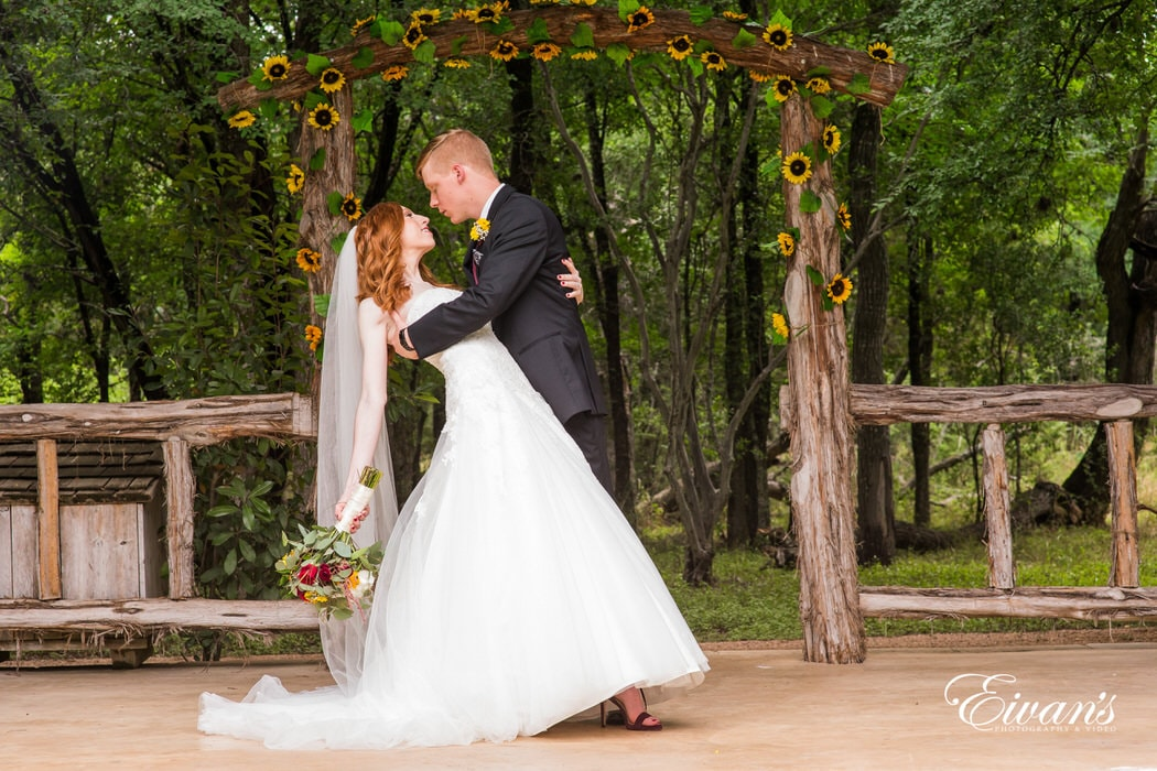 The groom holds his bride under a stunning sunflower arch gazing into one another's loving eyes.