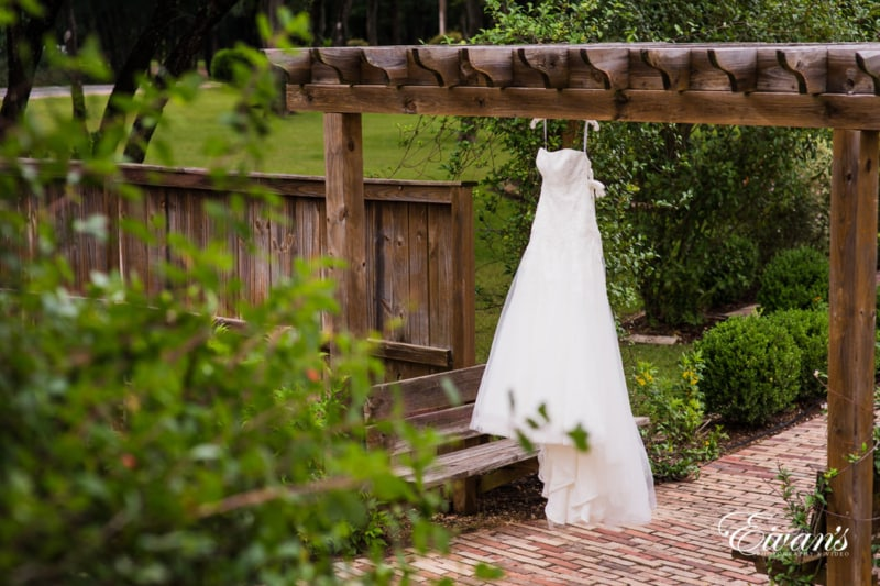 Pearly white wedding dress contrasting the bright greens and natural wood.