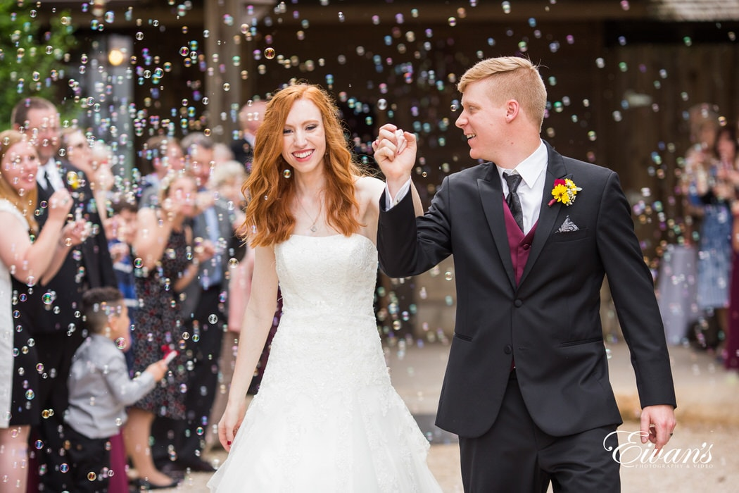 Smiling while exiting their ceremony the couple feels immense amounts of joy and pure happiness. Their friends and family blow bubbles while this moment is shared with all of them.