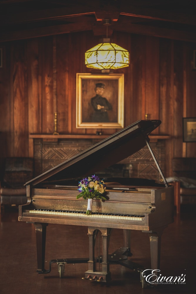 The bride's bouquet sits on a rustic piano, setting up a homey and caring environment.