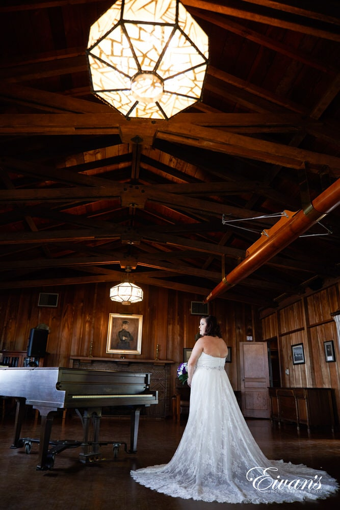 The bride stands in her beautiful white gown in this rustic environment.