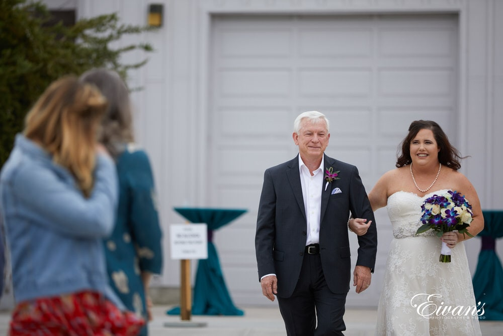 The bride walks down the isle with her father before being handed off to the love of her life.
