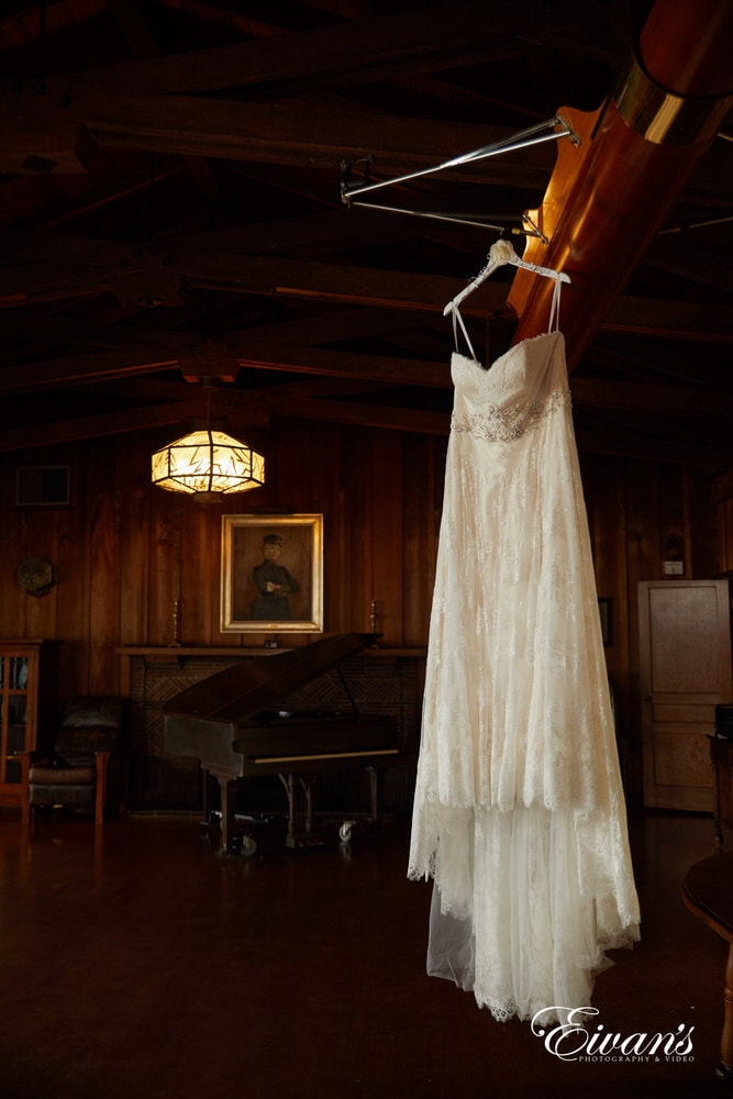 The bride's dress hangs in an amazing and rustic room filling and completing this couple's entire theme.