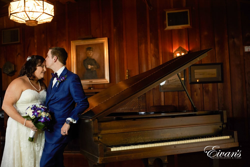 The couple lean against the piano together simply sharing this beautiful moment together.