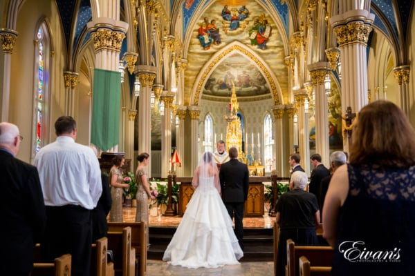 The outstanding couple stands in front of the priest as they make their eternal vows to one another to start their new lives together.