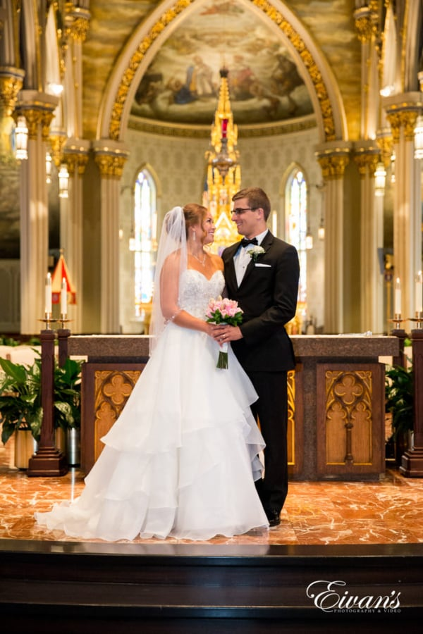 The couple stands at the front of the alter of this stunning chapel just gazing into one another's eyes. The look being shared between the two love birds is undeniable and demonstrates only true love and pure chemistry.
