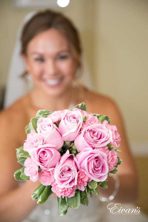 Chrissie smiles as she simply glows while holding her lovely bouquet of pink roses.